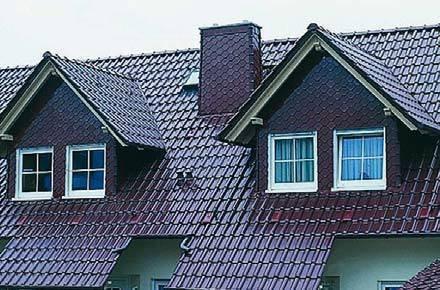 """Dach pokryty dachówką holenderką z kominem wyłożonym płytką ceramiczną w tym samym kolorze angoby. Na narożnikach komina ułożono małe gąsiory """"wieżowe"""". RuppCeramika"""