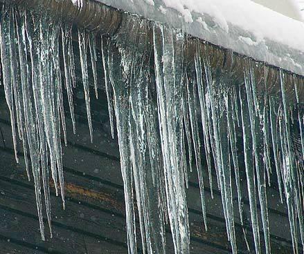 Plastikowa rynna obwieszona jest soplami i wypełniona czapą śniegowo-lodową powstałą na skutek topienia się i ubijania śniegu oraz zamarzania powstającej z niego wody. Jest to południowa strona budynku. Sople są skutkiem działania słońca i ucieczki ciepła z budynku. K. Patoka