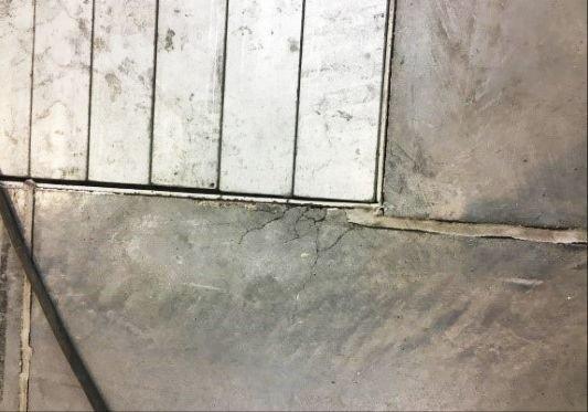 FOT. 7. Uszkodzona krawędź betonu przy korycie kablowym, masa elastyczna odspojona od betonu (hala nr 4); fot.: T. Majewski