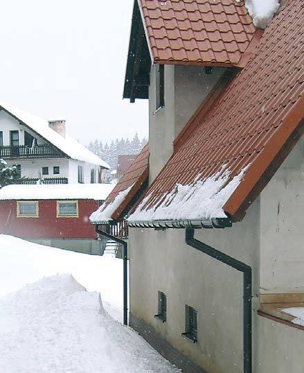 Fot. 3. Z metalowych (śliskich) pokryć dachów o dużym kącie nachylenia śnieg spada tuż po opadach. Na ziemi pod okapem widać sporą górę śniegu, który nie może utrzymać się na dachu, i rynny są całe, mimo że są wystające.