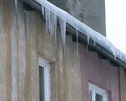Fot. 13. Strona wschodnia budynku. Stare pokrycie z blachy ocynkowanej przecieka, co jest przyczyną oblodzenia ścian. Sądząc z grubości lodu powstałego ze śniegu, a leżącego na rynnie, straty energetyczne przez dach są wysokie.