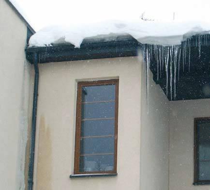 Fot. 14. Elewacja wschodnia. Zbyt krótkie obróbki blacharskie i źle skierowane pasy nadrynnowe powodują, że nawisy śniegu i lodu topnieją i powodują powstawanie oblodzenia ściany. Bardzo przezroczyste sople oznaczają, że straty ciepła przez dach w tym mi.