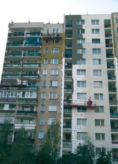 Fot. 1. Ocieplenie budynku wysokiego styropianem, a powyżej wysokości 25 m wełną mineralną. Zdjęcie ilustruje częstą, a niezalecaną praktykę: szpachlowanie łbów łączników mechanicznych
