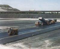 Fot. 2. Budowa uszczelniającej warstwy asfaltowej na zagęszczonym podłożu niecki wysypiska. Z lewej strony dostawa asfaltu do układarki i zagęszczarki warstwy asfaltu.