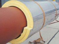 Fot. 5. Wygląd odcinka otuliny PUR na rurociągu. Uwagę zwraca przestrzeń technologiczna pomiędzy powierzchnią rurociągu a otuliną; w tym przypadku pustka powietrzna działa jako dodatkowa warstwa izolująca. Nieprzyleganie otuliny bezpośrednio do powierzchni rurociągu znacznie ogranicza przebieg ewentualnych procesów termicznego rozkładu PUR w kontakcie z rurą. W rogu: łubek otuliny.
