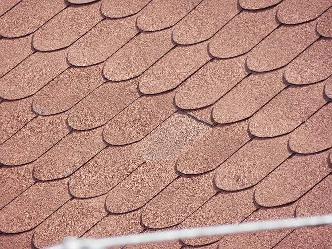 FOT. 2. Wyłamany element dachówkopodobnego wzoru gontu. Widać gwóźdź mocujący, który normalnie jest przykryty następnym arkuszem. Takie wyłamanie powstaje najczęściej na skutek działania wiatru i nierównego podłoża (dach z FOT. 3, 4).