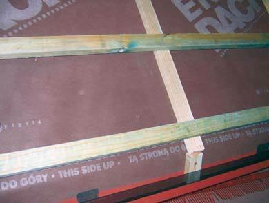 Fot. 9. Zdjęcie eksponatu szkoleniowego pokazującego prostszą odmianę okapu z oddolnym wlotem powietrza wentylującego pokrycie. Zamiast deski zastosowano obróbkę tworzącą kapinos zamocowany do krokwi. Pod eksponatem widać leżącą kratkę (opcja)