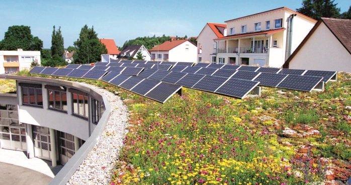"""System """"SolarGrünDach"""" firmy Optigrün jest instalowany jako układ unieruchamiany bez konieczności przebijania dachu. W tym celu stojaki do instalacji fotowoltaicznych Sun-Root są unieruchamiane poprzez obciążenie strukturą dachu zielonego. Optigrün international AG"""